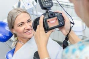 רופא מצלם במצלמה מקצועית שיניים של מטופלת