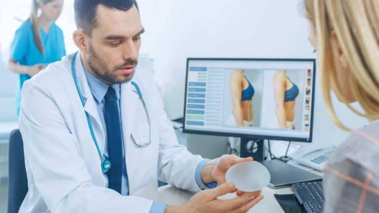 מנתח פלסטי מראה לאישה את השתל