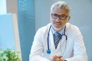 רופא עם משקפיים מחייך בשילוב ידיים