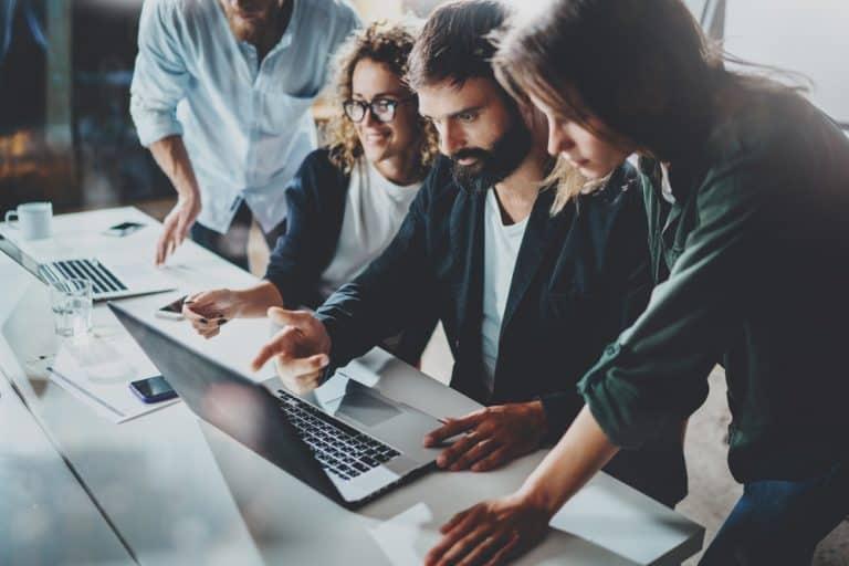 שתי נשים ושתי גברים מסתכלים על מסך מחשב נייד