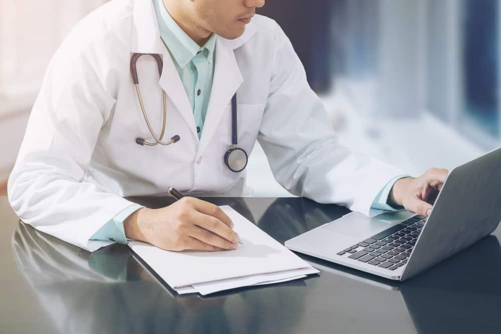 רופא מעתיק כתיבה תוכן מדף נייר למחשב נייד